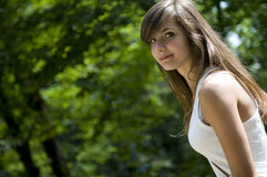 Brown hair smiling woman. Attractive young woman in park Royalty Free Stock Photography