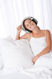 Brown hair woman with headphones sitting on sofa Stock Photo