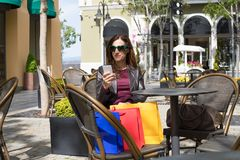 Woman in bar oudoors watching mobile with shopping bags Royalty Free Stock Photos