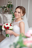 Brown-haired bride with classic wedding hairstyle, smiling taking wedding bouquet in her hands. stock image