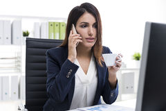 Brown haired businesswoman with a smartphone and a cup of coffee Royalty Free Stock Photo