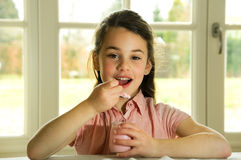 Brown haired child eating yogurt Royalty Free Stock Photos
