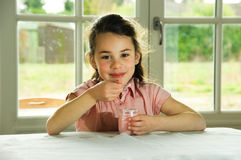 Brown haired child eating yogurt. Healthy lifstyle image Royalty Free Stock Image