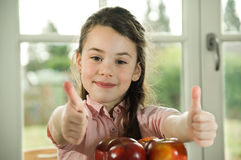 Brown haired child giving thumbs up for apples Royalty Free Stock Photo