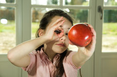 Brown haired child holding an apple Stock Images
