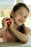 Brown haired child presenting an apple Stock Image