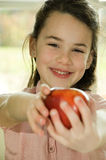 Brown haired child presenting an apple Royalty Free Stock Photography