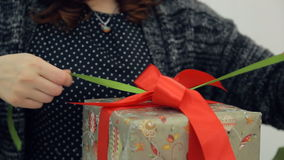 Brown-haired designer ties bow on packing new year present isolated stock video