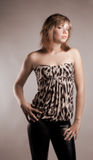 Brown-haired girl dressed in a tiger. Leopard fabric poses in the studio Royalty Free Stock Image