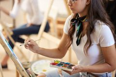 Brown-haired girl in glasses dressed in white t-shirt and jeans with a scarf around her neck paints a picture in the art stock images