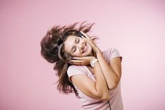 Brown-haired girl with headphones listening to music with closed eyes on pink background stock photo