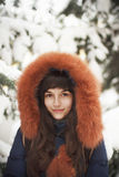 Brown-haired girl in the hood with fur smiling on a background of snow-covered trees Royalty Free Stock Photo