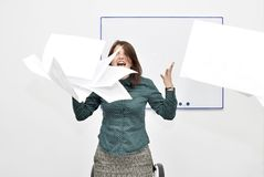The brown-haired girl in the office in rage threw up papers and documents. The concept of emotional manifestation in dissatisfaction with the result. Template stock photos