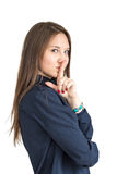 Brown-haired girl in a shirt presses a finger to her lips. Secretive Royalty Free Stock Images