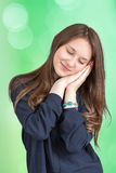 Brown-haired girl in shirt smiling in his sleep. The brown-haired girl in shirt smiling in his sleep on a green background Royalty Free Stock Image