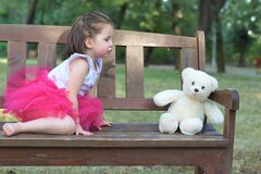 Brown Haired Girl Wearing Pink Tutu Dress Near White Bear Plush Toy stock photography