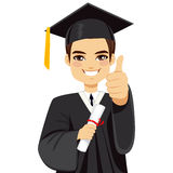 Brown Haired Graduation Boy. Happy brown haired boy on graduation day with diploma and making thumbs up hand gesture Royalty Free Stock Photo