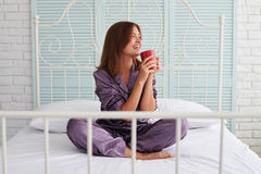 Brown-haired lady in pajamas drinking her morning coffee on bed Royalty Free Stock Photography