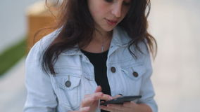 Brown-haired pretty caucasian girl with amazing smile in light white jeans coat using her smartphone, looking off the. Camera in the urban landscape background stock footage