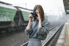 Brown Haired Woman in Gray 3/4 Sleeved Dress Holding a Camera Royalty Free Stock Photo