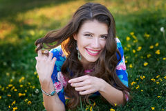 Brown-haired woman smiles in a summer green glade with flowers Stock Photos
