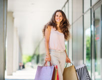 Brown-haired woman smiling about her successful shopping spree. A brown-haired woman wearing muted, gentle shades holds five colourful, patterned shopping bags stock images