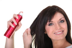 Brown-haired woman spraying her hair Royalty Free Stock Image