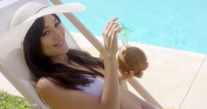 Brown haired woman in white bikini with sun hat stock footage
