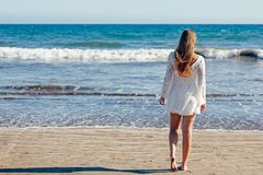 Brown Haired Woman in White Lace Long Sleeve Mini Dress Standing on Seashore Royalty Free Stock Image