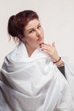 Brown-haired woman in a white sheet Royalty Free Stock Images