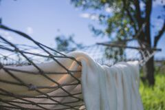 Brown Hammock With Towel Near Trees Royalty Free Stock Images