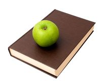 Brown hardcover book and green apple Stock Image