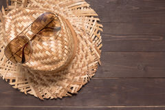 Brown hat and sunglasses are on the wooden background Stock Images