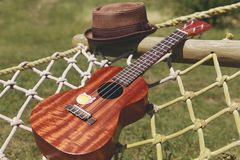 Brown hat and ukulele placed on a hammock stock photography