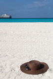 Brown hat on white sand. Brown hat and glasses on a white sand beach Royalty Free Stock Image