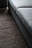 Brown hemp rug and fabric couch setting Stock Photography