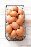 Brown Hen Eggs in a Chicken Wire Tray. On a wooden panel surface royalty free stock photos