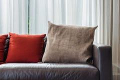 Brown i czerwona poduszka na nowożytnej kanapie Zdjęcie Stock
