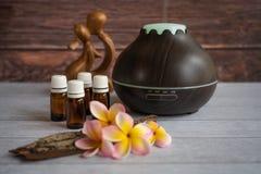 Brown istotnego oleju dyfuzor z frangipani kwiatami, świeczką i małą drewnianą miłości statuą, fotografia royalty free