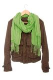Brown jacket and green scarf are on hanger. Royalty Free Stock Photography