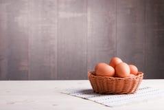 Brown jajka w łozinowym koszu na lekkim drewnianym stole i stronie Fotografia Royalty Free