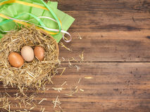 Brown jajka w siana gniazdeczka eco Wiejskim tle z brown kurczak słomą na tle stare drewniane deski i jajkami Fotografia Royalty Free
