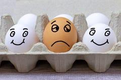 Brown jajko z twarzy wyrażeniem smutny między dwa białymi szczęśliwymi jajkami zdjęcie stock