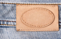 Brown jeans label. Brown leather jeans label sewed on jeans Royalty Free Stock Image