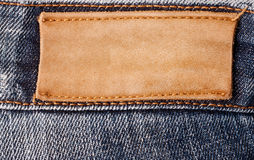 Brown jeans label. Brown leather jeans label sewed on jeans Stock Photo