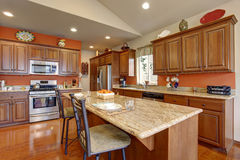 Brown kitchen room interior with granite counter tops and steel appliances. Stock Image