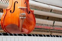 Brown klasyczny skrzypce na fortepianowej klawiaturze z inside ściany pianina tłem zdjęcie stock