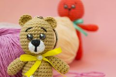 A brown knitted bear sits on a pink background, behind it is a ball of pink and yellow yarn, and an orange knitted hare stands. Behind the yarn. There is a royalty free stock photo