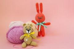 A brown knitted bear sits on a pink background, behind it is a ball of pink and yellow yarn, and an orange knitted hare stands. Behind the yarn. There is a royalty free stock photos
