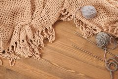 Brown knitted plaid and yarn on wooden background stock photography